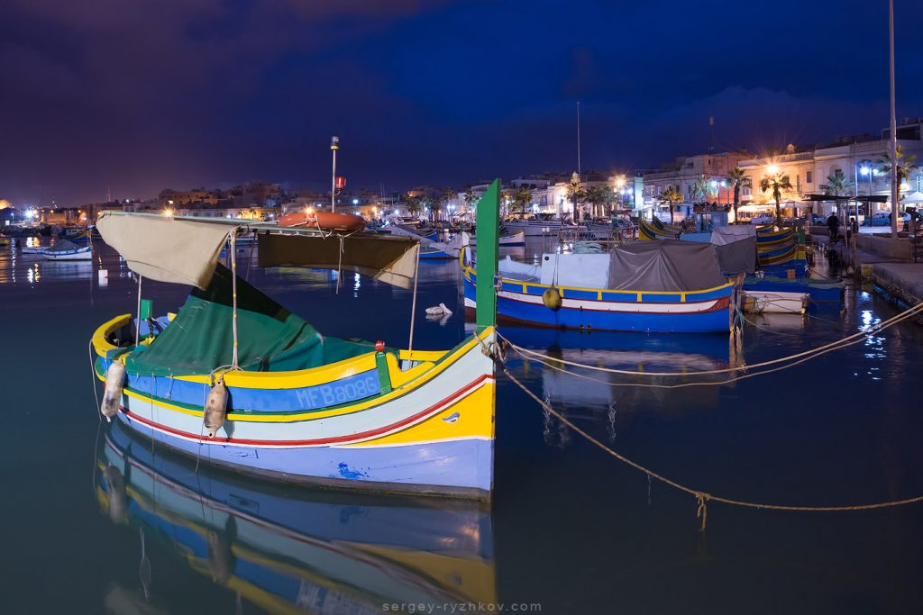 Traditional Maltese boats luzzu in Marsaxlokk at the night