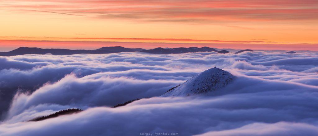 Вершина гори Хом'як виринає з вранішніх туманів зимою