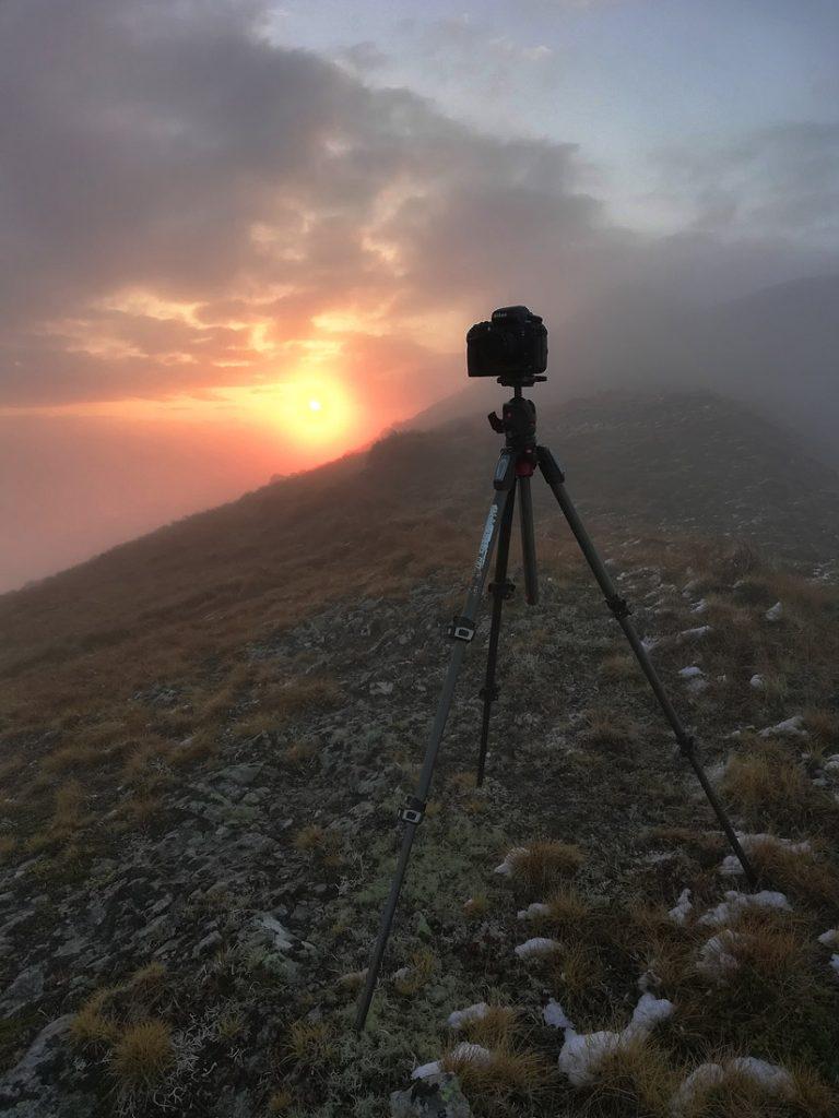 Фотокамера на штативі на фоні заходу сонця