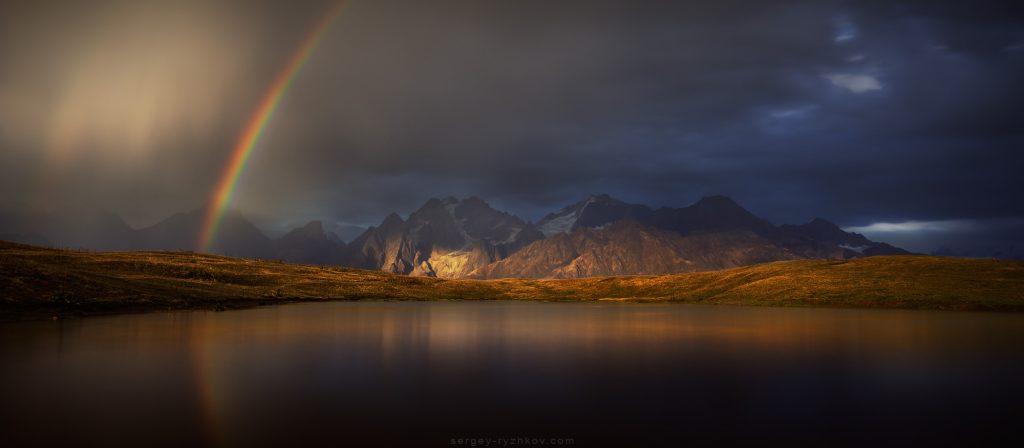 Веселка над озером на тлі Кавказьких гір